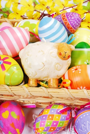 colorful decoration with easter painted eggs and sheep figurine in wicker basket photo