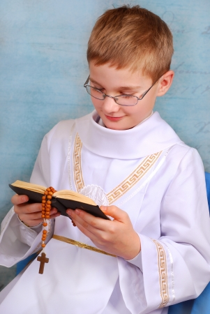 young boy in white alb going to the first holy communion and praying with prayer book photo