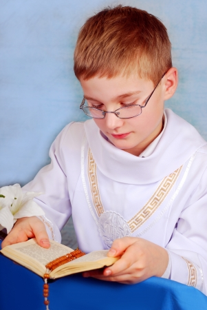 young boy in white alb going to the first holy communion and praying with prayer book Stock Photo - 18264713