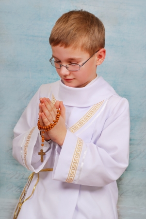 young boy in white alb going to the first holy communion and praying with wooden rosary photo