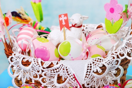 decoration with easter painted eggs and sheep figurine in wicker basket photo
