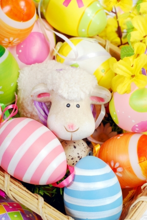 colorful decoration with easter painted eggs and sheep figurine in wicker basket