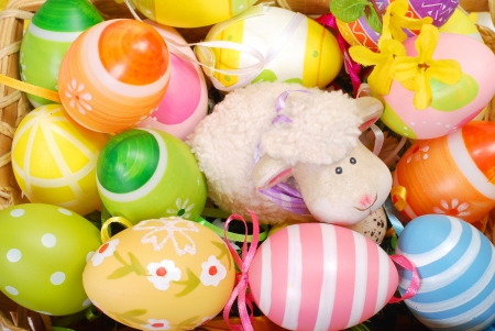 colorful decoration with easter painted eggs and sheep figurine in wicker basket (top view) photo