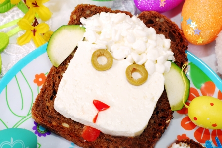 funny easter sandwich with sheep head made from cottage cheese on dark bread as breakfast for child Standard-Bild