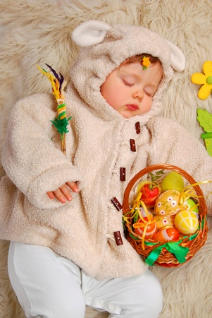 sleeping baby girl as easter sheep holding wicker basket with colorful eggs Stock Photo - 18311119