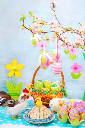 easter table with colorful eggs decoration in basket and hanging on cherry branch  photo
