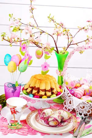 easter table decoration with marble ring cake and eggs in wicker basket photo