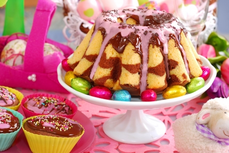 chocolate eggs: homemade marble ring cake poured chocolate sauce and pink icing on easter table
