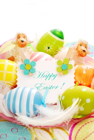 colorful painted easter eggs and greetings card  on the plate with feathers photo