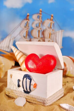 red heart and shell in wooden box on the beach as summer holidays concept photo