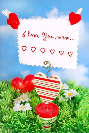 wooden decoration with heart in pot and greeting card for mom on the grass against blue sky photo
