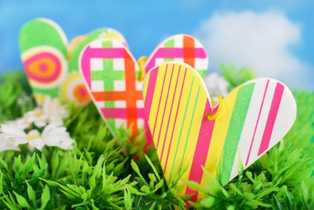 three colorful wooden hearts in the grass as symbol of spring love photo