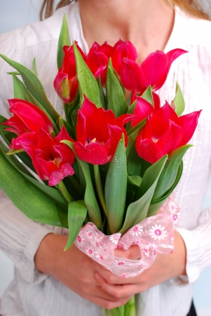 girl holding in hands a bouquet of red tulips  photo