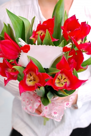 hands holding a bouquet of red tulips with ticket for message photo