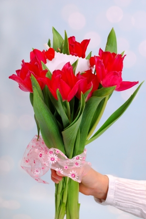 hand holding a bouquet of red tulips with ticket for message photo