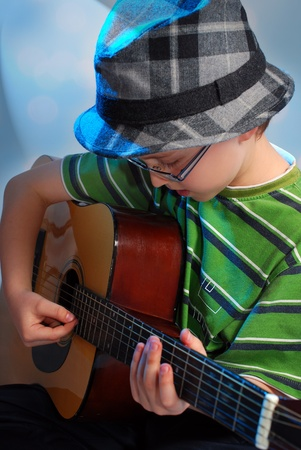 young boy in hat playing the classical guitar on stage photo