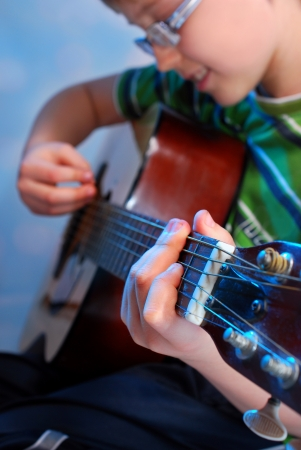 young boy playing the classical guitar on stage photo