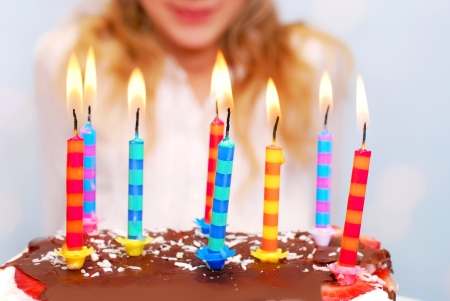 girl blowing: young girl celebrates birthday and blowing candles on the cake