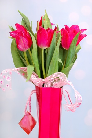 bouquet of pink tulips in gift bag on the table photo