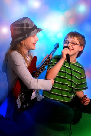 young girl playing the bass guitar and boy singing with microphone on stage photo