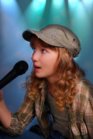 beautiful young girl singing with a microphone on the stage photo