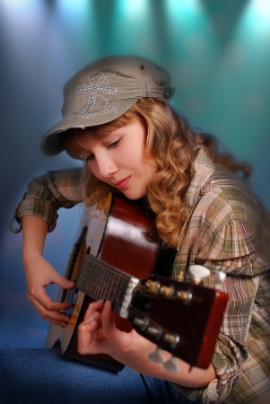 talent show: beautiful young girl playing acoustic guitar on the stage