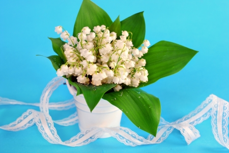lily of the valley bunch in little vase and white ribbon on blue background photo