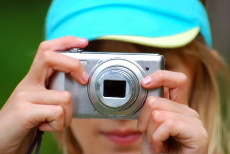 compact camera: closeup on hands of the girl taking photos by digital camera outdoor