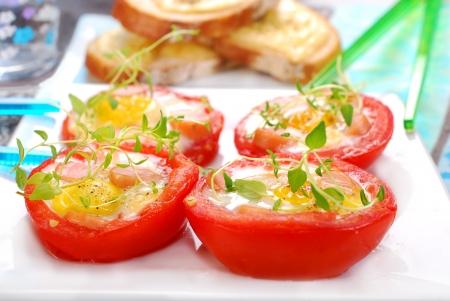 huevos de codorniz: mitades de tomate al horno rellenas con huevos de codorniz y chorizo Foto de archivo