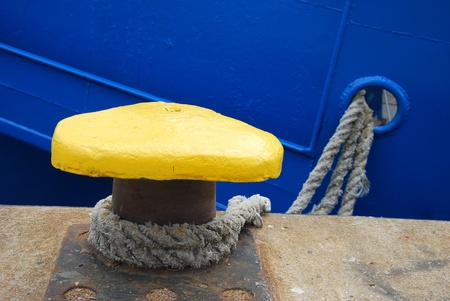 mooring: yellow mooring bollard with rope securing ship in the port