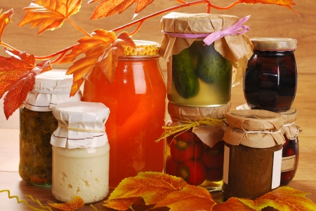 jars of homemade vegetables;fruits and mushrooms preserves in autumn scenery  photo