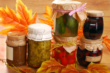 cherry varieties: jars of homemade vegetables;fruits and mushrooms preserves in autumn scenery