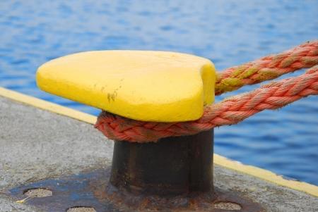 mooring: yellow mooring bollard with rope in the ship port