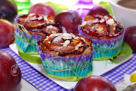 delicious muffins with plums in rose shape and almond flakes photo