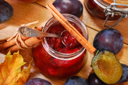 jam:  jar of homemade plum jam with cinnamon and fresh fruits on wooden table - top view