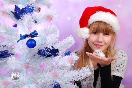 young girl in santa hat holding white hamster as christmas gift