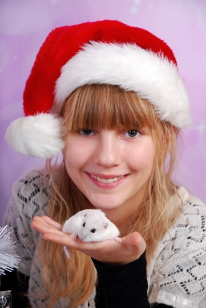 young girl in santa hat holding white hamster as christmas gift -focus on hamster