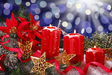 christmas decoration with three red candles in star shape on dark blue background photo