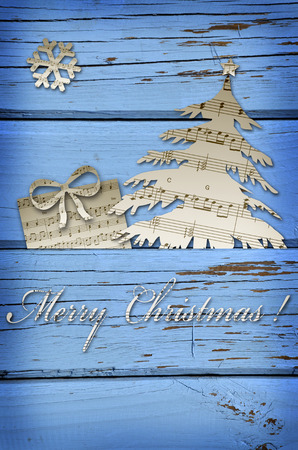 carol:  greetings card with christmas tree,gift and snowflake cut from vintage music sheets on blue wooden background