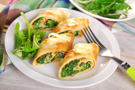 rolled pancakes stuffed with spinach and feta cheese cut into small pieces photo
