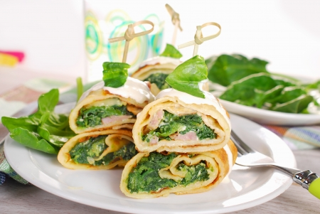 rolled pancakes stuffed with spinach ,bacon and feta cheese as shashlik on stick photo
