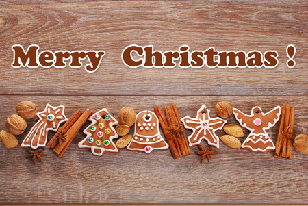 christmas border with gingerbread cookies decorated with icing and spices on wooden background photo