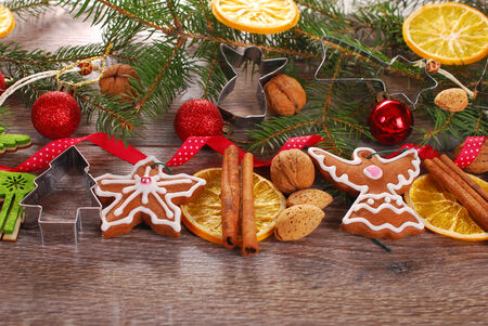 christmas decoration border with gingerbread cookies,fir,nuts and spices on wooden background photo