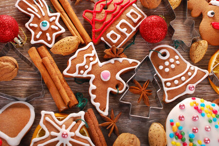 christmas background with homemade gingerbread cookies,cutters,spices and nuts on wooden board Stock Photo - 24238221