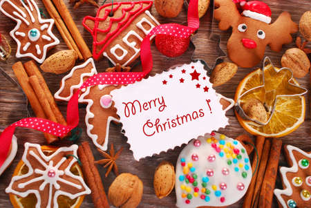 christmas background with greeting card , homemade gingerbread cookies,cutters,spices and nuts on wooden board Stock Photo - 24238224