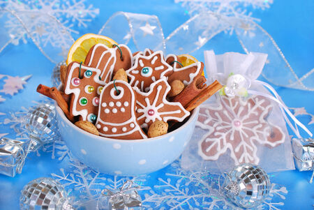 bowl of homemade christmas gingerbread cookies decorated with icing on blue background photo