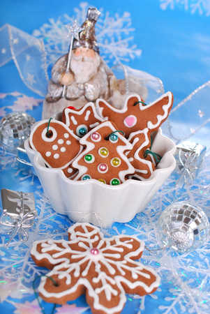 angel figurine: bowl of homemade christmas gingerbread cookies decorated with icing on blue background