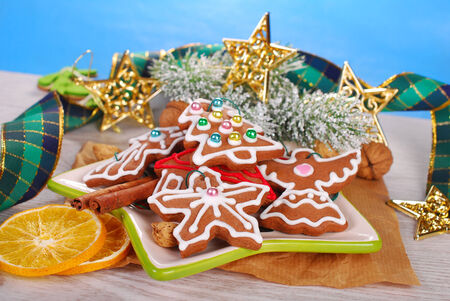 christmas decoration and plate of gingerbread cookies,nuts and spices on white wooden background photo