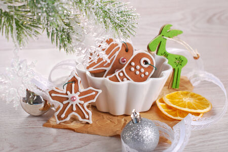 homemade christmas gingerbread cookies decorated with icing in white bowl photo