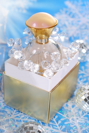 bottle of perfume standing on golden box in christmas scenery photo
